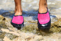 Water shoes in pink neoprene on rocks on beach closeup detail of the feet of a woman wearing bright Stock Photography