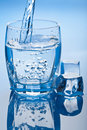 Water splashing into glass with ice cubes Royalty Free Stock Photography