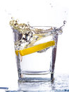 Water splashing up a slice of lemon falls into a tumbler Stock Photography
