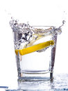 Water splashing up a slice of lemon falls into a tumbler Royalty Free Stock Images