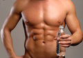 Water sport shaped and healthy body man holding mineral bottle Royalty Free Stock Photos