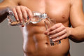 Water sport shaped and healthy body man holding mineral glass and bottle Stock Photos