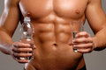Water sport shaped and healthy body man holding mineral glass and bottle Royalty Free Stock Photography