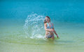 Water spray young woman beating the with his hands and makes a splash Stock Photos