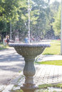 Water spreading everywhere near the road of the park with people resting and enjoying the sunlight Stock Photo