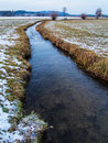 Water stream flowing in a field small through winter Stock Photo