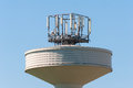Water tank tower surmounted with a telephone repeater antennas Royalty Free Stock Photo