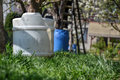 Water tank for watering the grass. Container to retain rainwater in the garden. White plastic jerrycan. Gallon water reserve Royalty Free Stock Photo