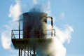 Water tower covered by steam old vintage industrial over clear blue sky Royalty Free Stock Photos