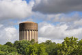 Water tower on a stormy day in tyler texas trees surround the the bottom with blue sky top with storm clouds rolling through Royalty Free Stock Images