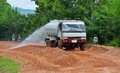 water truck sprays water on  new road construction project. Royalty Free Stock Photo