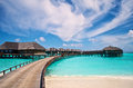Water villas and wooden jetty of the resort in the maldives lagoon with blue sky Stock Photos