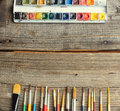 Watercolor professional aquarell paints in box with brushes on old wooden board Stock Images