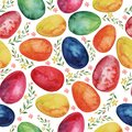 Watercolor seamless pattern with colored Easter eggs and spring plants.