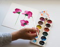 Watercolors, painting of beautiful pink flowers, hand holding a brush, on white background, artistic workplace