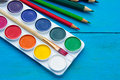 Watercolors and pencils on blue wooden background. Royalty Free Stock Photo