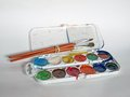 Watercolors plastic box with cheap and brushes Royalty Free Stock Photo