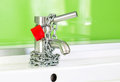 Waterdrop dripping out modern faucet locked red lock chain Royalty Free Stock Image