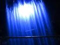 Waterfall curtain by night behind the illuminated dark blue scene Royalty Free Stock Photos