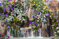 Waterfall and flowers in garden background Royalty Free Stock Photos