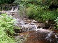 Waterfall flowing downstream beautiful tranquil softly past the rocks in large garden Stock Photos