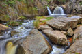 Waterfall with granite rocks stream of water from a small between Stock Image