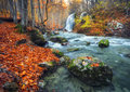 Waterfall at mountain river in autumn forest at sunset. Royalty Free Stock Photo