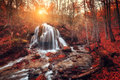 Waterfall at mountain river in autumn forest at sunset Royalty Free Stock Photo