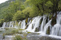 Waterfall picture of beautiful the running water among green trees Stock Image