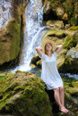 Waterfall rest beautiful young woman in white sundress and straw hat stopped to and dream near the among the mossy stones Royalty Free Stock Photos