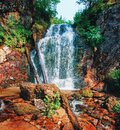 Waterfall among stones and taiga driftwood in water and wet stones Royalty Free Stock Photo