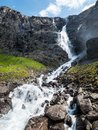 Waterfall and stream flowing on mountainside Royalty Free Stock Photo
