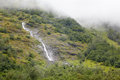Waterfalls in misty mountains. Royalty Free Stock Photo