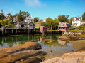 Waterfront cottages in fishing village small rental and fishermen homes over the water stonington harbor on deer isle maine Royalty Free Stock Images