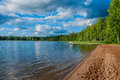 Beautiful deserted sandy beach of a forest lake with deckchairs and moored boats in the sun
