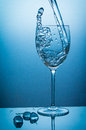 Waterglass and icecubes water being poured in a wine glass too fast water jumps out of the glass again Royalty Free Stock Photography