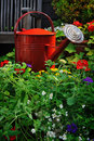 Watering Can Surrounded By Flowers Vertically Stock Photo