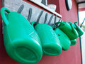 Watering cans hanging on horsehoes Royalty Free Stock Photo