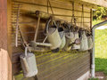 Watering cans and a rake row of metal hanging in front of wooden wall Stock Photo