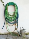 Watering garden hose and ewer tools coiled green hanging on the grey wall the with the sprinkler Royalty Free Stock Images