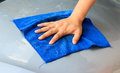 Waterless car wash. Men`s hand with blue cloth cleaning car Royalty Free Stock Photo