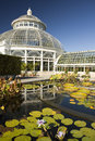 Waterlily pond and greenhouse in front of the green house at the new york botanical garden Royalty Free Stock Images