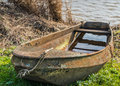Waterlogged old and rusty rowing boat neglected rusted on the banks of a lake partially filled with water Royalty Free Stock Photography