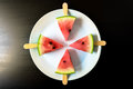 Watermelon cut slice on a stick from ice cream close-up on white plate on a black Royalty Free Stock Photo