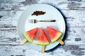 Watermelon cut slice on a stick from ice cream with fork close-up on white plate on an old vintage table Royalty Free Stock Photo