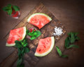 Watermelon drink watermelon pieces in a rustic wooden background.