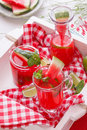 Watermelon lemonade in bottles and a glass freshly made drinks pieces of melon on rustic wooden tray Stock Photo