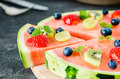 Watermelon pizza cut with fruits on wooden board, close up Royalty Free Stock Photo