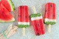 Watermelon popsicles with fresh melon slices on white marble