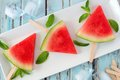 Watermelon slice pops on a white plate over rustic blue wood Royalty Free Stock Photo